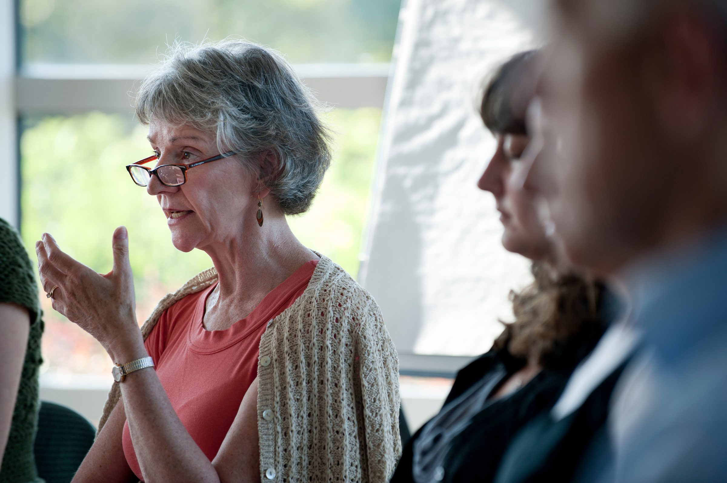 older adult woman speaking in a group