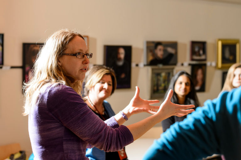 a teacher expressively talking to a group of students