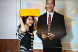 Student from China wearing a cheese head standing with cut-out of Obama