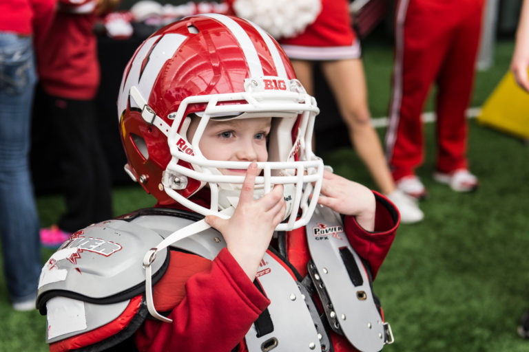 little boy wearing badger football uniform and helmet