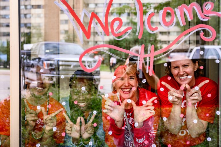 Move in welcome photo with people in the window
